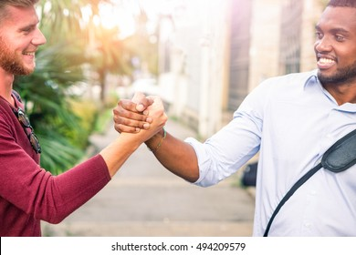 Interracial friends greeting each other with handshaking in the street cropped image - Young business men friendly hands gesture outdoors - Concept of friendship and different people relations
