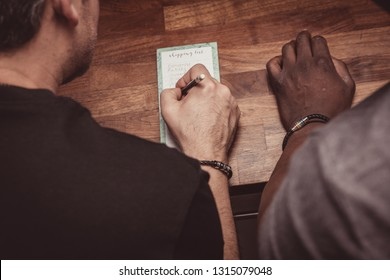 An interracial gay couple making a shopping list for groceries on a wooden kitchen top at home.