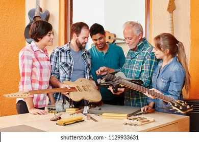 Interracial group of apprentices of luthier in his shop