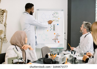 Interracial group of doctors, chemists, scientists having discussion in meeting while young African man telling new information and showing biochemical molecules of substances on the board.