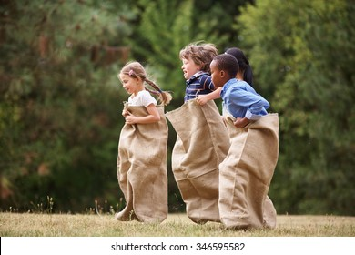Interracial group of kids competing at a sack race in summer