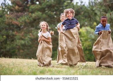 Interracial group of kids having fut at sack race