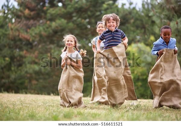 Interethnische Gruppe von Kindern, die beim Sackrennen fliegen
