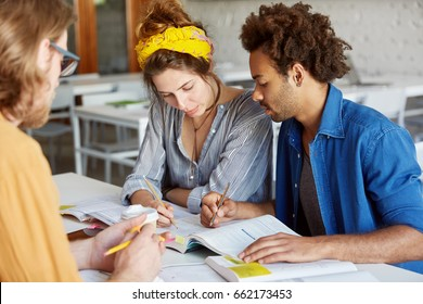Interracial group of students sitting at desk having concentrated look in book doing tests marking right answers with pencils posing against classroom interior. Education, cooperation, team concept
