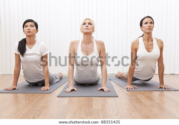 An interracial group of three beautiful young women stretching in a yoga position at a gym