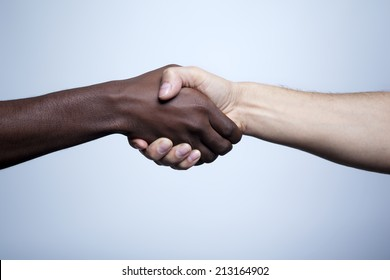 Interracial handshake on gray background