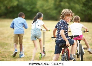 Interracial happy kids with bikes in nature