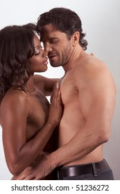 interracial heterosexual couple in sensual kiss. Mid adult Caucasian men in late 30s and young mulatto biracial female mix of black African American, Native American and German ethnicity in 20s
