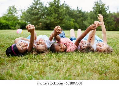 Interracial kids show togetherness holding hands as friends in summer