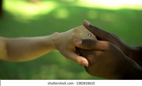 Interracial marriage ceremony, man holding woman hand with golden ring on finger
