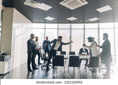 Interracial partners arguing during team building training meeting, Caucasian furious office worker disagreeing with Arabian colleague, dark-skinned and white businessmen disputing at negotiations