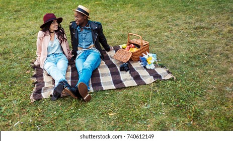 interracial smiling couple sitting on a blanket in the park and looking at each other