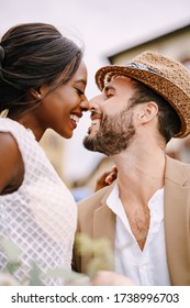 Interracial wedding couple. Wedding in Florence, Italy. A close-up of portraits of an African-American bride and Caucasian groom in a straw hat.