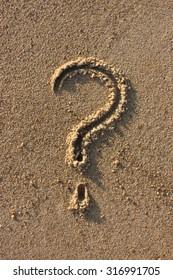 Interrogation point handwritten in sand on the beach, at sunrise.