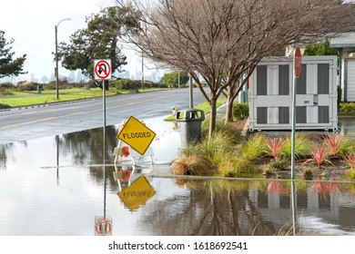 Intersection submerged, flooded after recent rains. Warning signs up to prepare drivers for possibly water damage to vehicle due to flooding, don't drive through flooded roads.