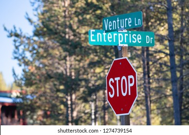 Intersection of Venture lane and Enterprise drive streets with a stop sign below them. Concept for free market and capitalism.