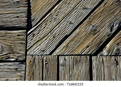 intersection of weather beaten gray wooden walkway in Yellowstone park with diagonal, horizontal and vertical lines coming together in a ninety degree intersection