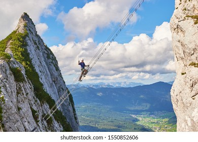 Intersport Donnerkogel via ferrata in Summer, with a man showing a victory sign while climbing the diagonal ladder. Stairway to heaven concept.