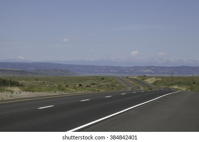An interstate road traveling toward the Sangre De Cristo Mountains.