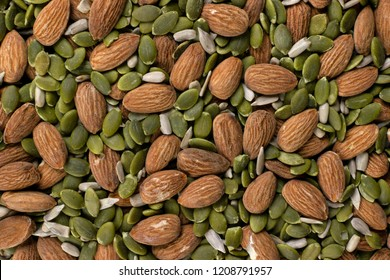 An intersting background texture closeup photo of a mixture of almonds, pumpkin seeds, and sunflower seeds mixed together to make a healthy snack like trail mix.