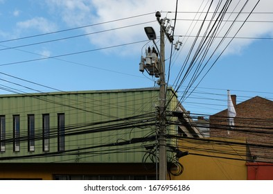 Intertwining of many telecomunication and electrical wires on pylon