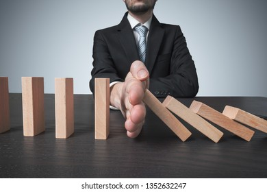Intervention concept. Man stops falling domino with hand.