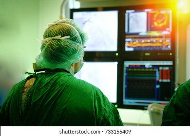 Interventional cardiology. Male surgeon doctor with coronary monitor in operating room.