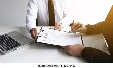 Interview employee is reading and checking a resume with a job applicant in the office, Job applications concepts.