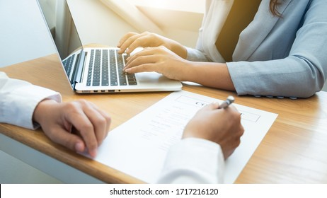 Interview employee is using computer notebook and checking a contract with a job applicant in the office, Job applications concepts.