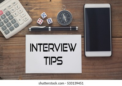 Interview Tips written on paper,Wooden background desk with calculator,dice,compass,smart phone and pen.Top view conceptual.