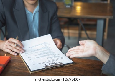 Interviewer reading a resume, Woman submits job application
