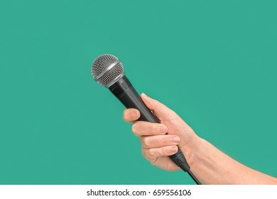 Interviewer or reporter with microphone in hand on green background, mic. Front view