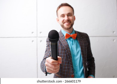The interviewer. Young bearded man in plaid suit with microphone. Focus on microphone.