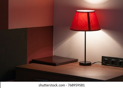 Intimate atmosphere in the hotel room. Bedside table on which lie the leather folder of the menu, do not disturb the sign and the lamp with a textile lampshade