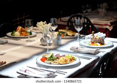 Intimate atmosphere in a restaurant with four served plates - beef steak, chicken, fish and appetizer