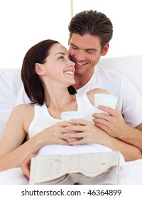 Intimate couple drinking orange juice lying in the bed