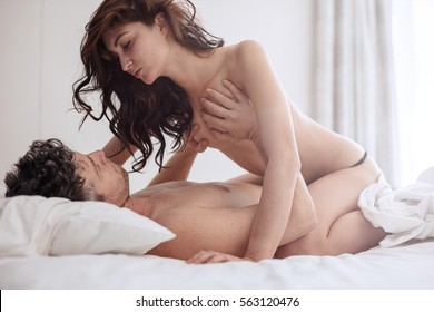 Intimate couple in sexual intercourse in bedroom.  Romantic young man and woman in love having sex.