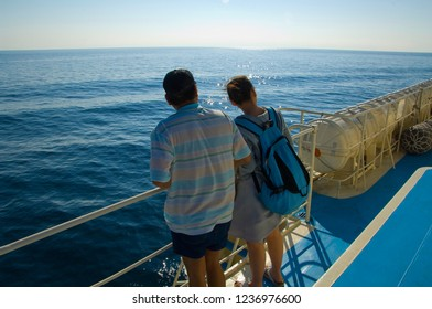 The intimate embrace of people is in stark contrast to the sailing yachts in the blue ocean.