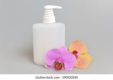 Intimate gel or liquid soap dispenser pump plastic bottle orchid flowers on gray background