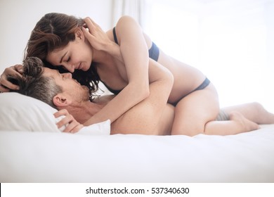 Intimate lovers making love in bed. Romantic and passionate young couple on bed.