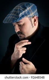 Intimate man portrait with hat on dark background.