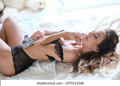 Intimate model pn white bedsheet posing with old fashioned camera.