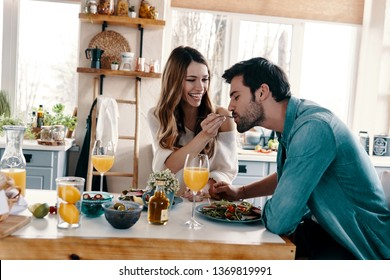 Intimate moments. Beautiful young couple enjoying healthy breakfast while sitting in the kitchen at home