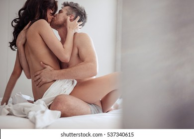Intimate young couple hugging and kissing. Man and woman in bed having passionate sex.