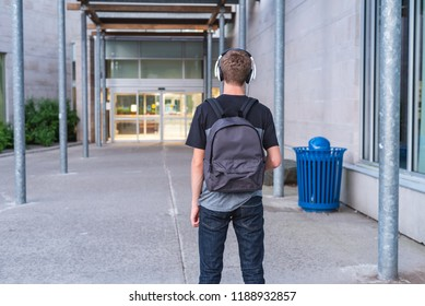 Intimidated teenager walking towards school while listening to music with his headphones.