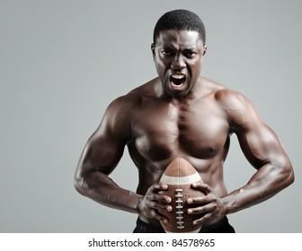 Intimidating portraits of a black american football sportsman in studio