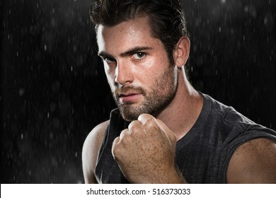 Intimidating pose fist raised male fighter manly masculine powerful stare MMA mixed martial arts rain