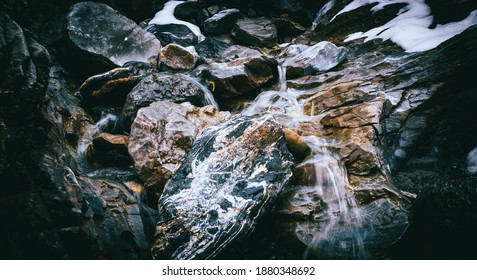 up into the mountain, surrounded by rocks and natural fresh water is coming out of the massive mountain, could be used as background decoration or wallpaper