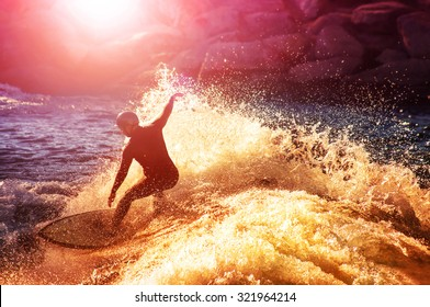into the sun photo of a surfer riding a wave in a full wet suit toned with a retro vintage instagram filter app or action effect (SHALLOW DOF and long shutter speed action shot)