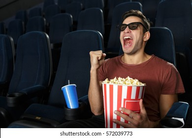 So into this film. Young emotional handsome man wearing 3D glasses shouting shaking his fist in victory gesture watching movie alone at the cinema entertainment excitement premier lifestyle copyspace